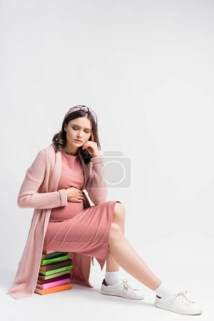 upset and pregnant woman sitting on books and touching belly on white