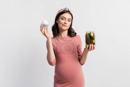 femme enceinte choisir entre cupcake et pot avec des concombres marinés isolés sur blanc