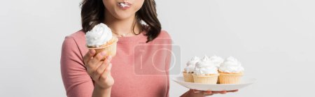 panoramic crop of woman holding plate while eating cupcake isolated on white