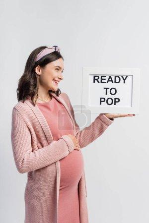 joyeuse et enceinte femme regardant bord avec prêt à pop lettrage isolé sur blanc