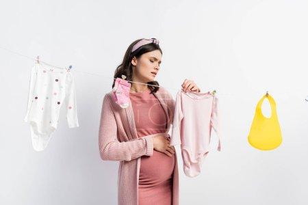 Photo pour Femme triste et enceinte pendre des vêtements de bébé sur la ligne de vêtements sur blanc - image libre de droit