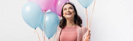 Photo pour Récolte panoramique de femme joyeuse dans le bandeau tenant des ballons et regardant isolé sur blanc - image libre de droit