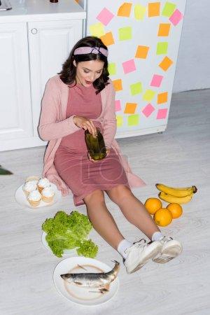 Photo pour Joyeuse femme tenant pot avec des concombres en conserve tout en étant assis sur le sol près de cupcakes et fruits - image libre de droit