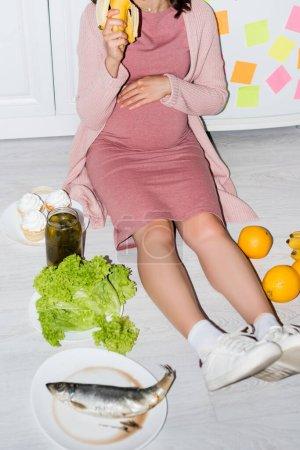 vista parcial de la mujer embarazada sosteniendo plátano cerca del frasco con pepinos enlatados, cupcakes y naranjas mientras está sentada en el suelo