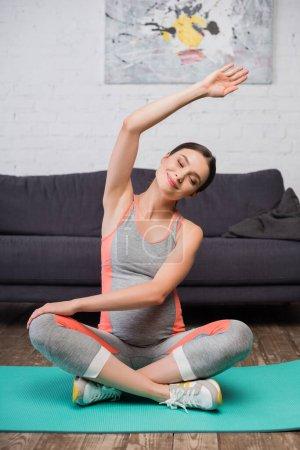 Photo pour Joyeuse femme enceinte avec les yeux fermés exercice sur tapis de fitness à la maison - image libre de droit