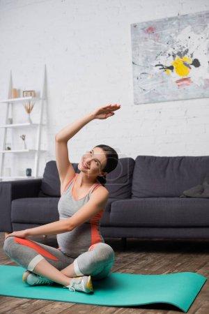 Photo pour Joyeuse femme enceinte faisant de l'exercice sur tapis de fitness à la maison - image libre de droit