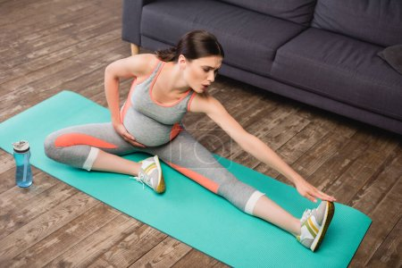 high angle view of pregnant woman in sportswear stretching on fitness mat