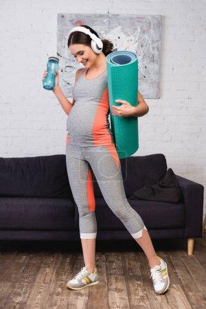 Photo pour Joyeuse femme enceinte dans un casque sans fil écouter de la musique tout en tenant tapis de fitness et bouteille de sport - image libre de droit