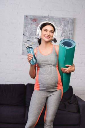joyful pregnant woman in wireless headphones listening music while holding sports bottle and fitness mat