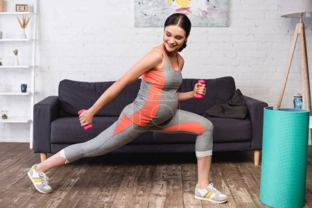Photo for Joyful pregnant woman exercising with pink dumbbells at home - Royalty Free Image