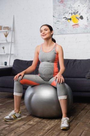 mujer embarazada complacida en ropa deportiva haciendo ejercicio en la alfombra de fitness en la sala de estar