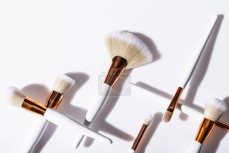 Photo pour Pose plate avec pinceaux cosmétiques fixés sur fond blanc avec espace de copie - image libre de droit