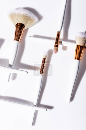 flat lay with cosmetic brushes set on white background