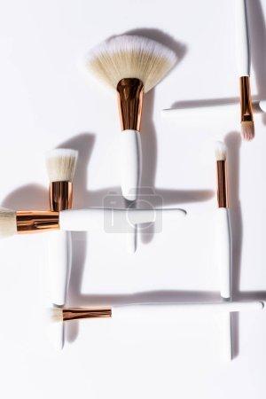 Photo pour Pose plate avec pinceaux cosmétiques fixés sur fond blanc - image libre de droit