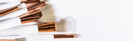 top view of cosmetic brushes set on white background with copy space, panoramic shot