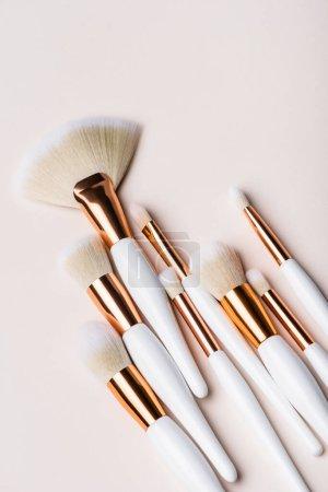 Photo pour Vue de dessus des pinceaux cosmétiques blancs et dorés sur fond beige - image libre de droit