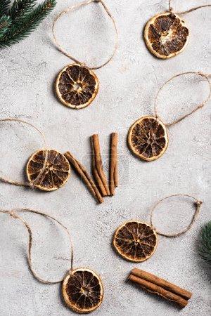 Vue de dessus des morceaux d'orange séchée avec cordes, bâtons de cannelle et branches de pin