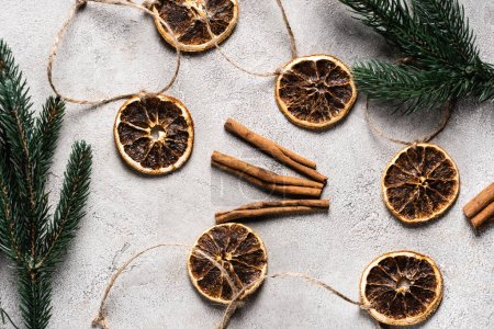Photo for Top view of dried orange pieces with cinnamon sticks on grey background - Royalty Free Image