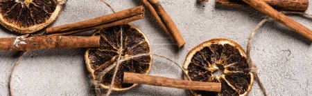 Photo for Panoramic shot of dried orange pieces and cinnamon sticks on grey background - Royalty Free Image