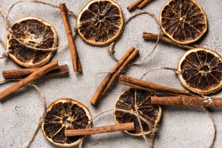 Top view of dried orange pieces and cinnamon sticks on grey background