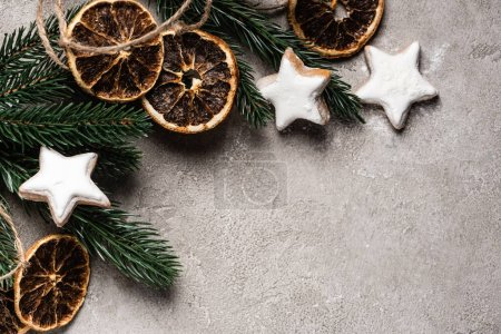 Photo for Top view of pine branch with dried orange pieces and cookies on grey background - Royalty Free Image
