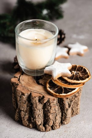 Selective focus of candle with dried orange slices and cookie on wooden stand