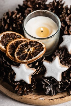 Scented candle with pine cones, dried orange slices and cookies