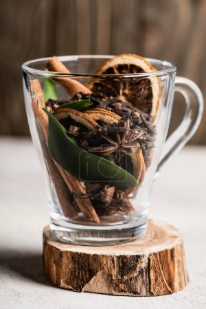 Photo for Selective focus of glass cup with spices and orange dried slices on wooden stand - Royalty Free Image
