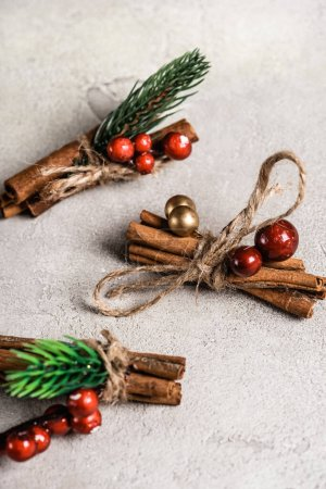 Cinnamon sticks with red beads on textured and grey background