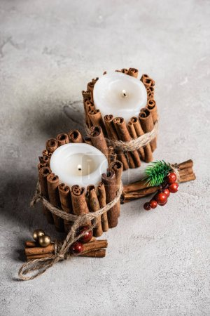 Photo for Scented candles decorated with cinnamon sticks on textured and grey background - Royalty Free Image