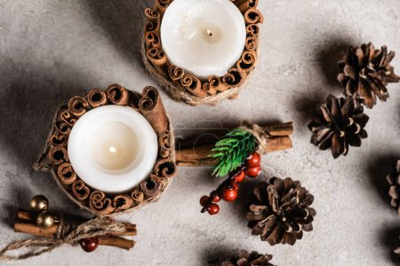 Top view of decorated candles with cinnamon sticks near pine cones and rowan