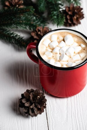 Selective focus of red cup of cocoa near pine cone on wooden background
