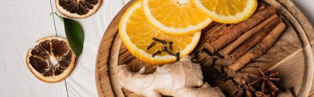 Panoramic shot of wooden plate with spices and fresh orange slices