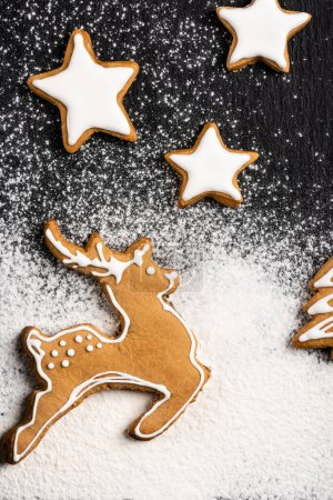 Photo for Top view of gingerbread cookies in shape of stars and deer with sugar powder - Royalty Free Image