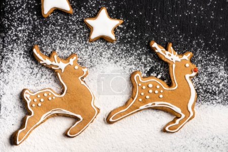 Photo for Top view of gingerbread cookies in shape of stars and deers with sugar powder - Royalty Free Image