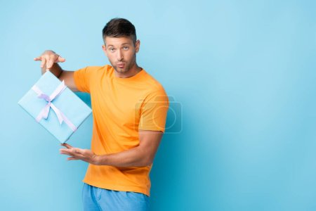 Mann im T-Shirt schmollende Lippen und hält verpackten Geschenkkarton auf blau