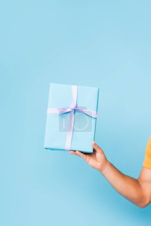 cropped view of man holding wrapped gift box on blue