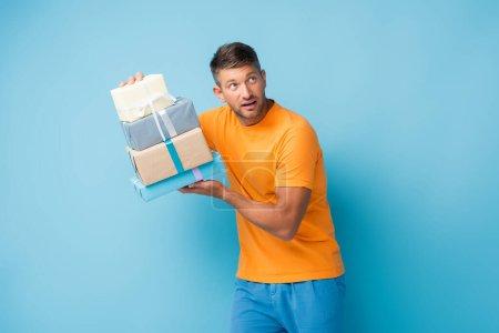 Neugieriger Mann im T-Shirt hält verpackte Geschenke in der Hand und schaut weg