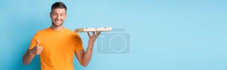 Photo pour Homme gai en t-shirt tenant boîte à pizza carton et montrant pouce vers le haut sur bleu, bannière - image libre de droit