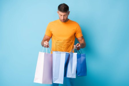 Photo for Shocked man in t-shirt holding shopping bags on blue - Royalty Free Image