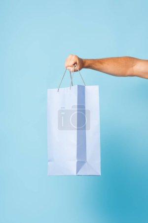 Photo pour Vue recadrée de l'homme en t-shirt tenant sac à provisions sur bleu - image libre de droit