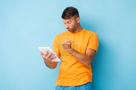 Photo pour Homme mécontent en t-shirt montrant poing serré tout en utilisant une tablette numérique sur bleu - image libre de droit