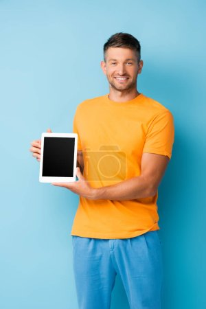 pleased man in t-shirt holding digital tablet with blank screen on blue