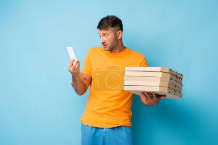 Mann im T-Shirt hält Pizzakartons in der Hand und blickt auf Smartphone auf blauem Grund