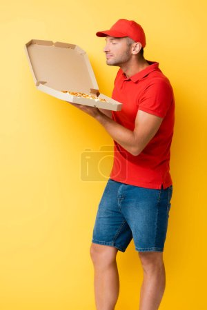 pleased delivery man in red cap smelling tasty pizza in carton box on yellow