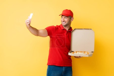 Photo for Smiling delivery man in red cap holding box with tasty pizza and taking selfie on yellow - Royalty Free Image