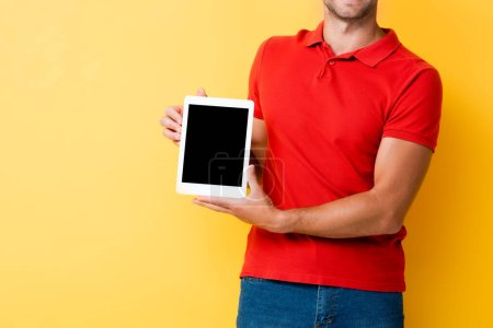 Photo for Cropped view of man holding digital tablet with blank screen on yellow - Royalty Free Image