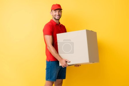 happy delivery man in red cap holding carton box on yellow
