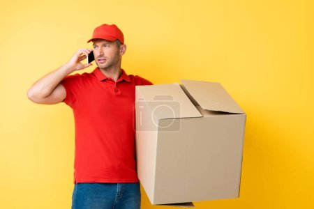 delivery man in red cap holding carton box and talking on smartphone on yellow