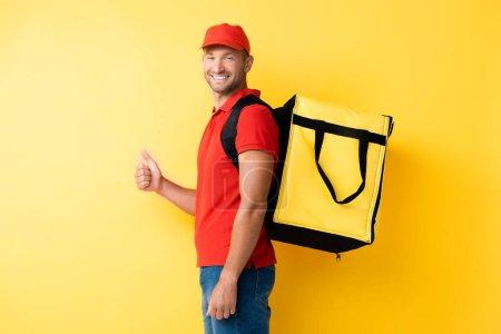 Photo pour Livreur joyeux portant sac à dos avec ordre et montrant pouce vers le haut sur jaune - image libre de droit